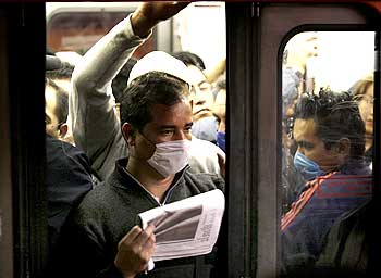 Passengers wearing protective masks ride on Mexico's city subway