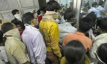 People wearing masks wait in a queue for a H1N1 flu screening at a hospital in New Delhi