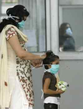 A mother puts on a surgical mask for her daughter as they arrive for a flu screening at Ram Manohar Lohia hospital in New Delhi