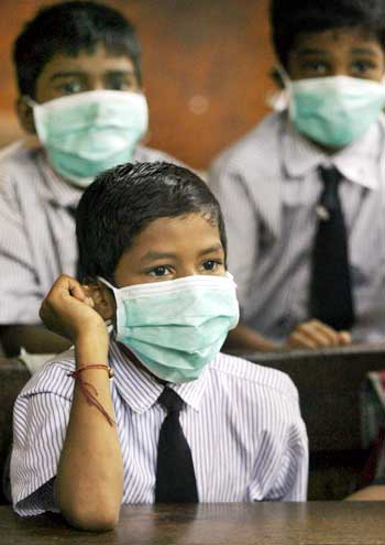 Children wearing masks sit in a classroom at a school in Mumbai