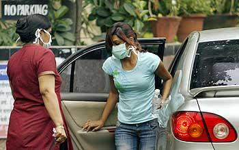 People wearing masks arrive outside a special ward for H1N1 influenza testing at the Kasturba Hospital in Mumbai
