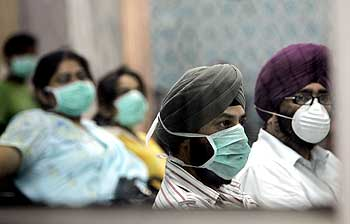 People wearing surgical masks wait for a H1N1 flu screening at Ram Manohar Lohia hospital in New Delhi
