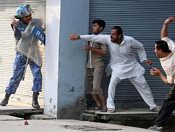 Demonstrators throw stones at a Rapid Action Force soldier during a protest in Jammu against the government's decision not to give forest land to a trust that runs Amarnath cave shrine