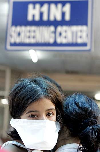 A woman carries her daughter as they wait for a H1N1 flu screening at a hospital in New Delhi