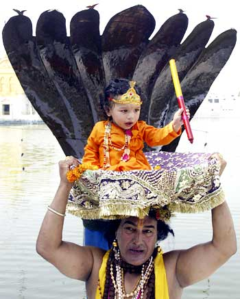 A devotee carries a child dressed as Krishna in a basket at the Durgiana temple on the eve of Janamashtmi in Amritsar