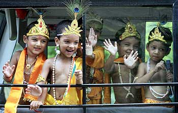 School children dressed as Krishna wave from inside a bus on the eve of Janamashtmi celebrations in Chandigarh