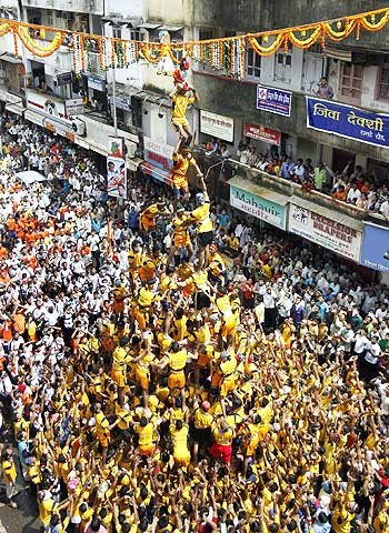 Devotees form a human pyramid to reach a clay pot containing butter during the celebrations