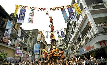 Female devotees form a human pyramid to break a clay pot containing butter during the celebrations