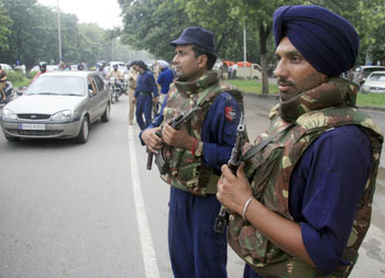 Police stand guard on the eve of India's Independence Day celebrations in Chandigarh