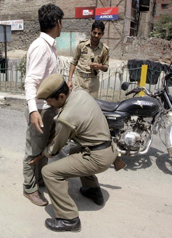 A policeman searches a youth ahead of Independence Day celebrations in Srinagar