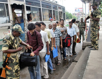 A policeman checks the bag of a bus passenger as others wait in a queue for their turn in Guwahati