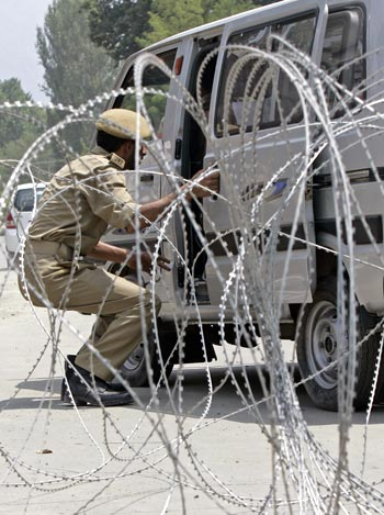 A policeman inspects a car ahead of Independence Day celebrations in Srinagar