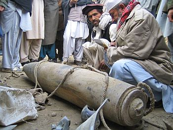 Pakistani tribesmen near an unexploded missile in a village in Zamzola area