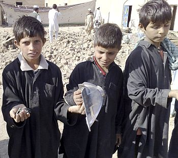 Boys show off broken pieces of suspected US missiles in the Janikhel tribal area in Bannu district