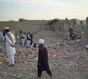 Villagers gather at a damaged house after a missile strike in Dandi Darpakheil village