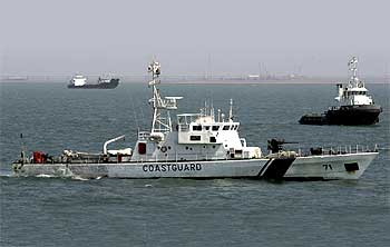 A coast guard vessel takes part in a training exercise conducted under the national oil spill disaster contingency plan at the Gulf of Kutch