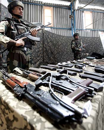 A soldier stands guard near seized arms and ammunition at an Army garrison in Kupwara, Kashmir