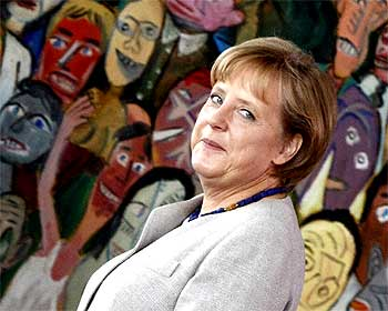 German Chancellor Angela Merkel passes in front of the painting 'Der 9. November' by German artist Hans-Peter Zimmer in the Chancellery in Berlin