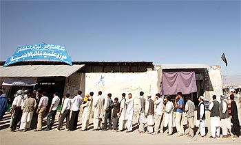Afghan men wait in line to vote in a polling station during the presidential election in Kabul
