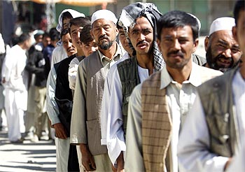 Men queue up to vote in the presidential election at a polling station in Kabul