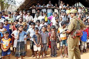A Sri Lankan policeman stands guard over displaced Tamil civilians.