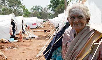 An elderly Tamil woman sits in front of a row of tents in a refugee camp located near Vavuniya.