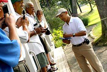 Obama signs autographs for golfers before his round of golf at Mink Meadows Golf Club