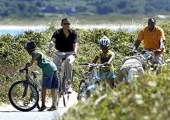 Obama rides a bike with his daughter Sasha (Centre) in Aquinnah on Martha's Vineyard
