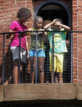 Malia (Left) and Sasha (Centre) Obama step out onto the balcony of Gay Head Lighthouse with an unidentified friend