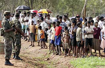 Soldiers stand guard near IDPs at the Vavuniya camp
