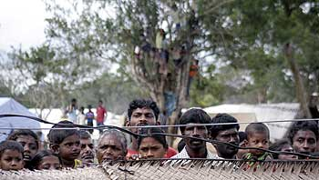 IDPs look over a fence as they stand inside a camp in Vavuniya
