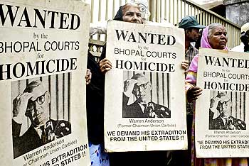 Victims hold wanted poster of former Union Carbide chairman Warren Anderson during a protest outside a court in Bhopal
