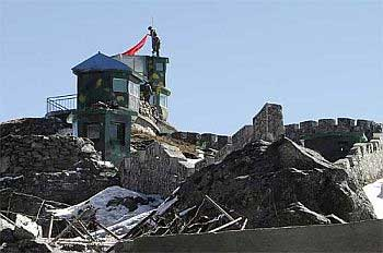 Chinese soldiers put up a flag atop their post at the India-China trade route at Nathu-La Pass.
