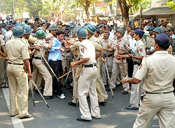 Police personnel detain a protestor