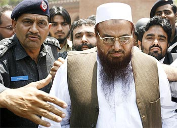 Police escort Hafiz Sayeed, head of the banned Jamaat-ud-Dawa and founder of Lashkar-e-Tayiba, as he leaves after an appearance in court in Lahore