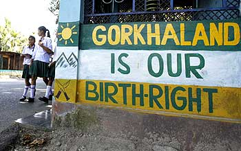 Schoolgirls walk past a graffiti demanding statehood for Gorkhaland at Sukuna in Darjeeling