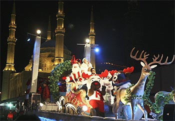 A float carrying performers dressed as Santa Claus and his assistants tours in front of al-Amin mosque during a Christmas parade in downtown Beirut
