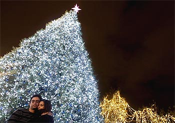 A couple hugs in front of a Christmas tree during a lighting ceremony at central Syntagma square in Athens