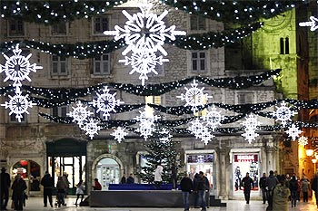 People walk past Christmas lights in the Adriatic city of Split in Croatia