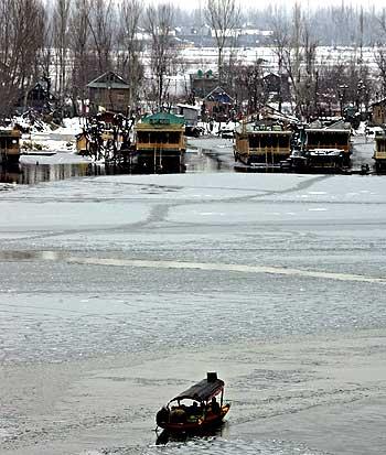 Kashmiris sit on a boat in the partially frozen Dal Lake in Srinagar