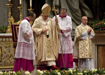 Pope Benedict XVI is assisted as he leads the Christmas mass in Saint Peter's Basilica at the Vatican