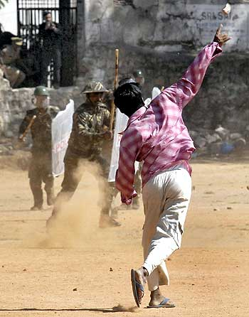 A pro-Telangana supporter throws a a brick at police during a protest in Hyderabad