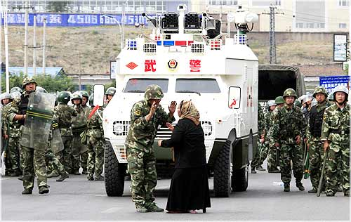 A woman on a crutch argues with a Chinese soldier in front of an armoured personnel carrier and soldiers wearing riot gear