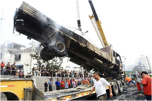 A truck, which was destroyed in Sunday's riot, is hoisted