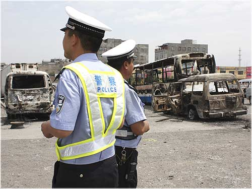 Policemen stand in front of vehicles, which were destroyed during Sunday riot in Urumqi