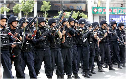 Chinese riot police get into position as Uighur protesters gather during a demonstration