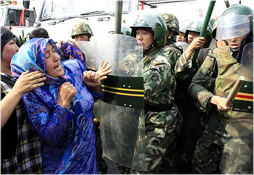 A woman pushes at Chinese soldiers wearing riot gear as a crowd of angry locals confront security forces on a street