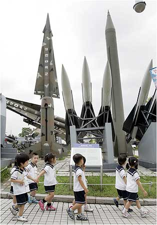 Pupils walk past models of a North Korean Scud-B missile and South Korean missiles at the Korean War Me