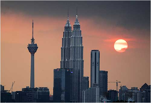 The sun sets near the Petronas Twin Towers (C) and Kuala Lumpur Tower