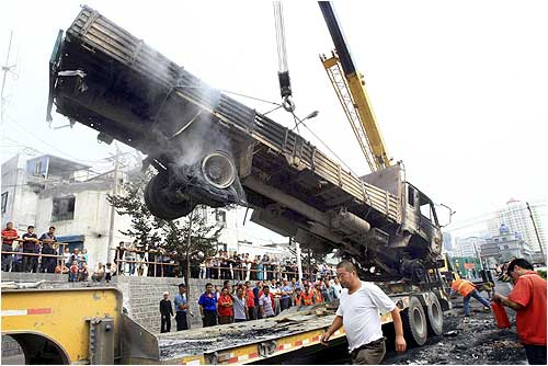 A truck which was destroyed in Sunday's riot is hoisted in Urumqi, Xinjiang Uigur Autonomous Region.
